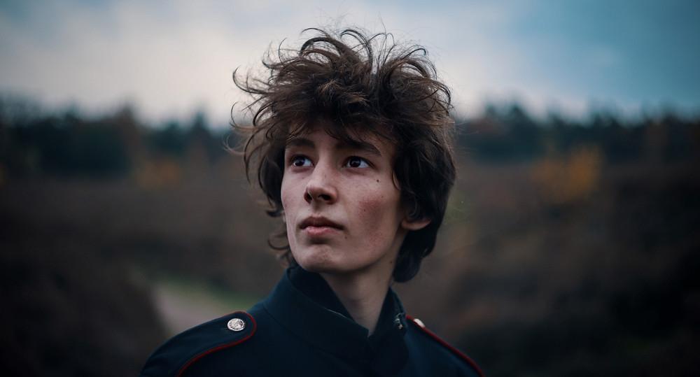Een portret foto van een jonge man in een natuurgebied. De man met donker haar kijkt met een serieuze blik iets om hoog de verte in.