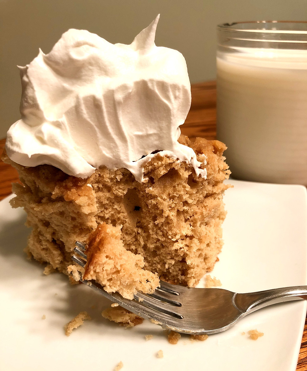 A fork sits in front of a piece of brown crumbly cake, with a piece cut and ready to eat.  The cake is topped with white whipped topping and a glass of white milk sits behind the plate of cake.