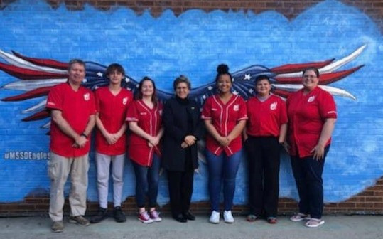 Academic Bowl team and coaches posing in front of MSSD Eagles painting with Bobbi Cordano, the president of Gallaudet University.