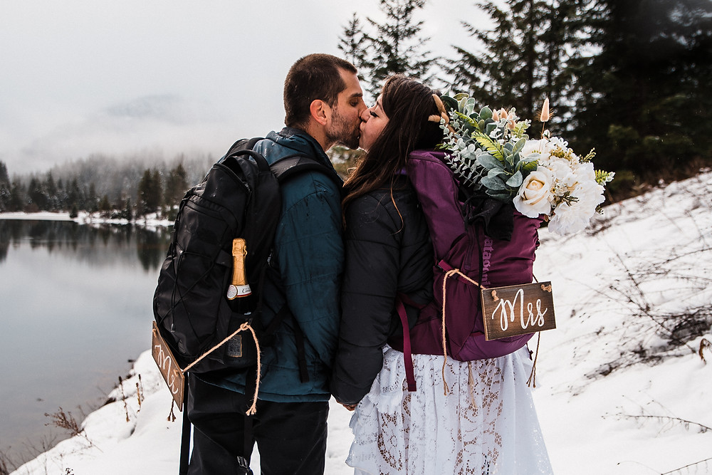 A couple kissing on their elopement day in a snowy winter setting. Their backpacks have cute Mr and Mrs signs on them