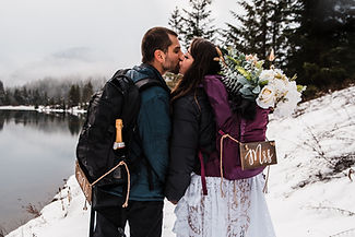 A couple kissing during their snowy backpacking elopement in Washington