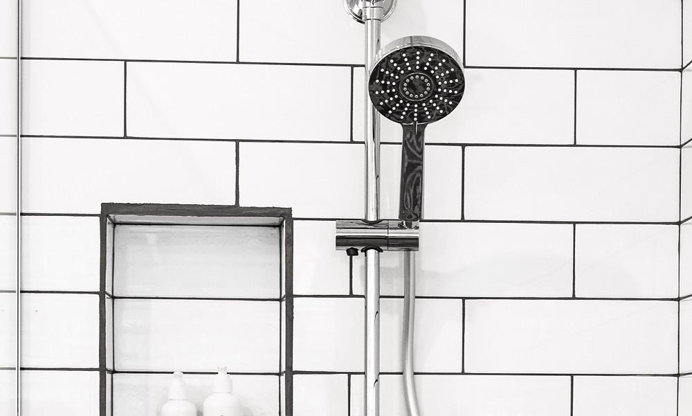 Shower head mounted on bathroom wall in bathtub
