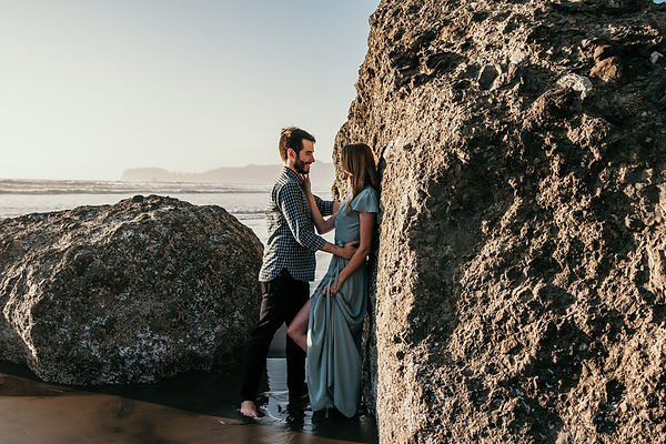 A couple leaning up against a rock on the Washington coast during their engagement photos