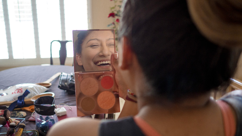 Sister of the bride laughing into her makeup mirror
