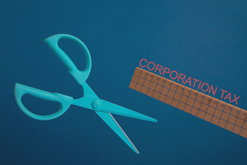 A pair of scissors, a wooden ruler and the words Corporation Tax