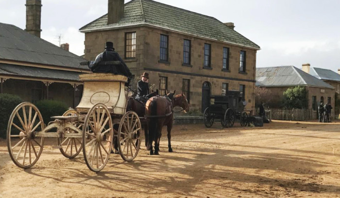 A carriage drawn by two horses down a dirt road outside a large building.