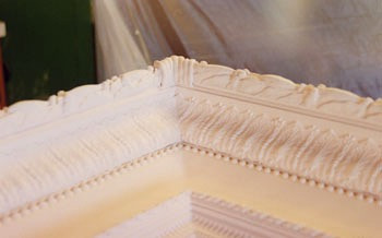 Several coats of gesso are applied to the raw frame, giving it a hard, smooth surface to accept the gilding.