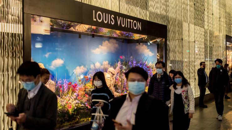 Pedestres em frente a Louis Vuitton usando máscaras na reabertura do mercado depois durante a pandemia
