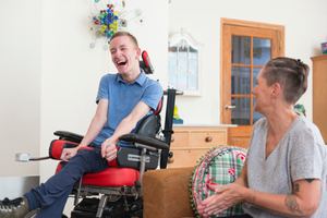 Young man grinning from wheelchair, carer assists him with respite care