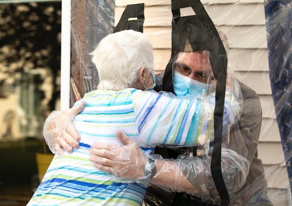 Woman hugs a man through a plastic shield, wearing a mask and gloves to protect from COVID-19