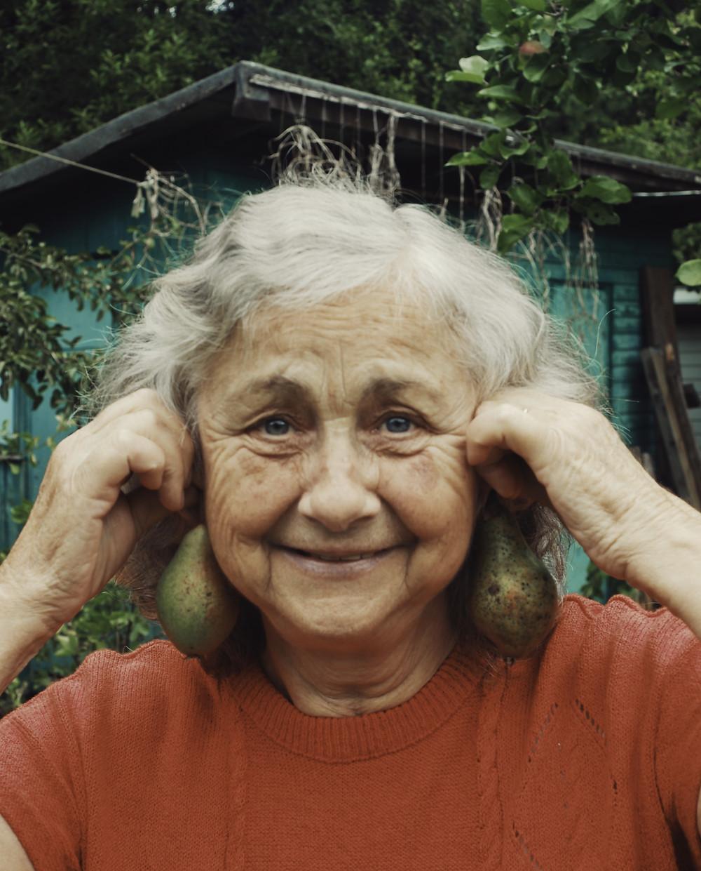 Grandma holding avocadoes as earrings