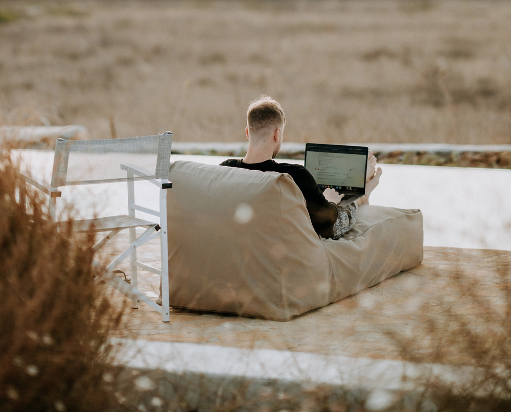 A man workig on a PC on a Chaiselonge outside. The ground around him looks dry and it could be summer