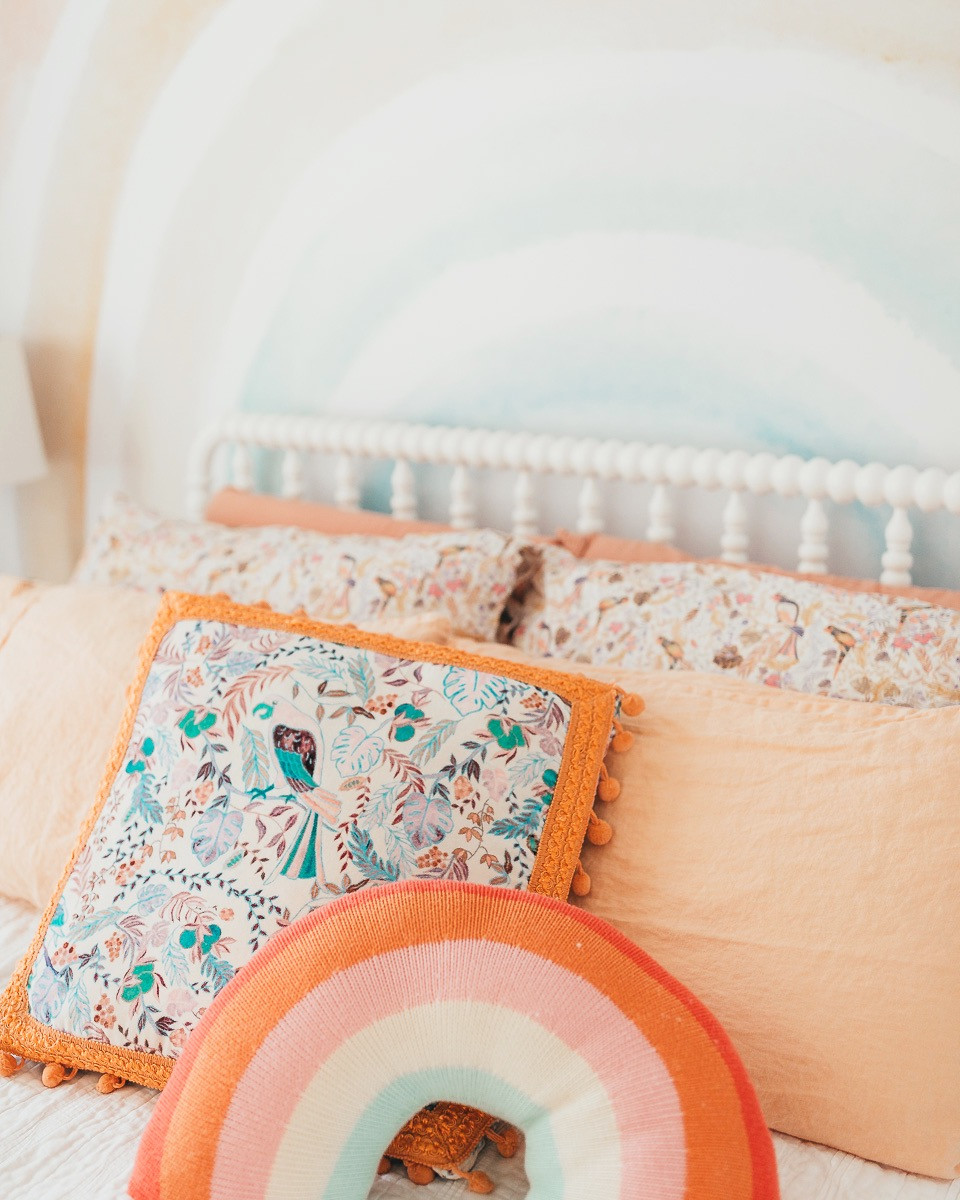A floral pillow on a soft vintage bed next to a rainbow pillow in a kids rainbow themed bedroom.