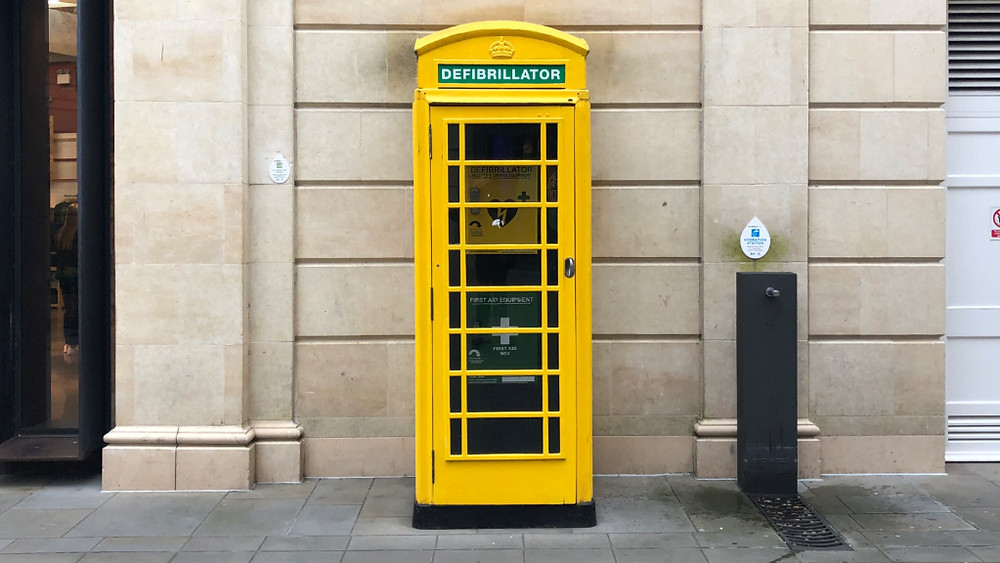 Red phone box turned into a yellow emergency response station with defibrillator and first aid kit