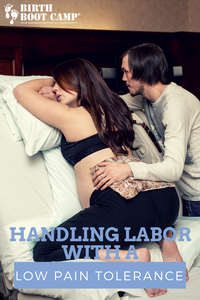 Laboring woman leans over hospital bed while partner applies heat pad to her back.
