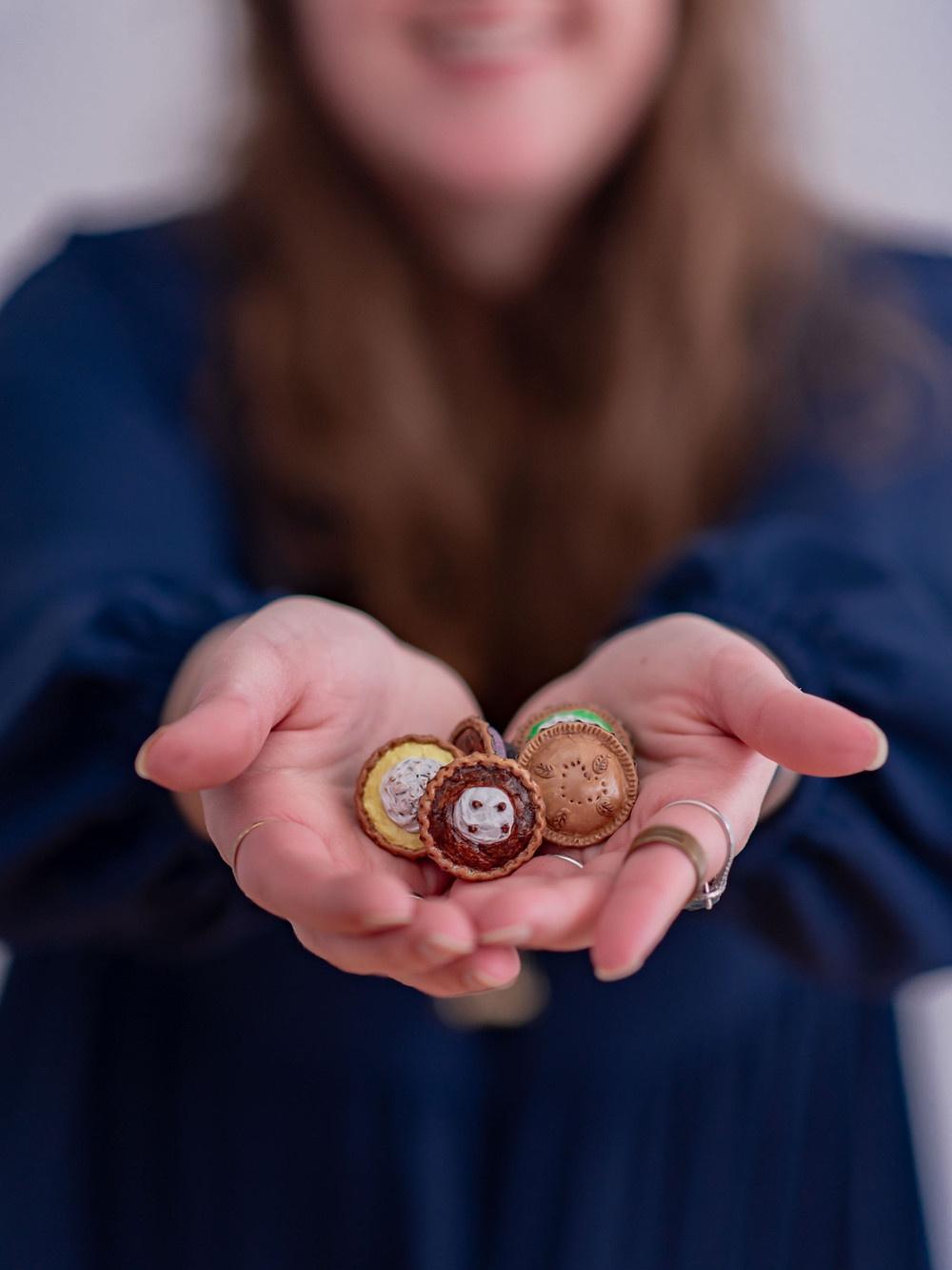 Hands offering miniature pies with a smiling face in the background