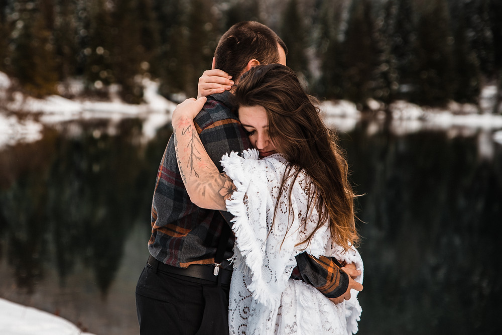 A couple embraces during their elopement day at a snowy Gold Creek Pond in Washington