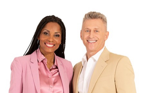 Julie Soimaud, a black woman dressed in pink pant suit with matching pink shirt, is standing to the right of her husband Jerome Soimaud who is dressed in khaki suit and white shirt