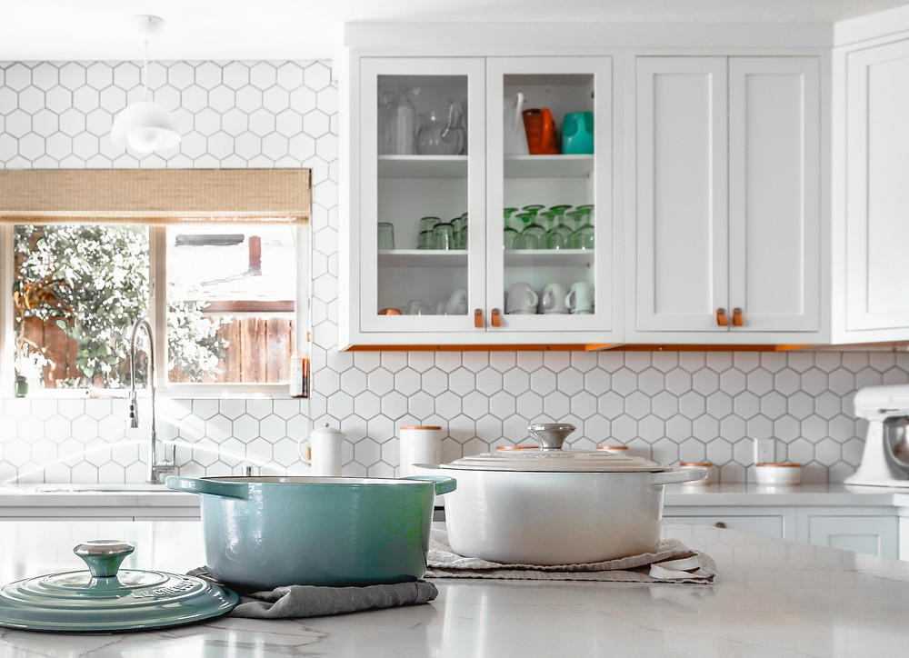 Pots on kitchen countertop with white pantry items neatly stored