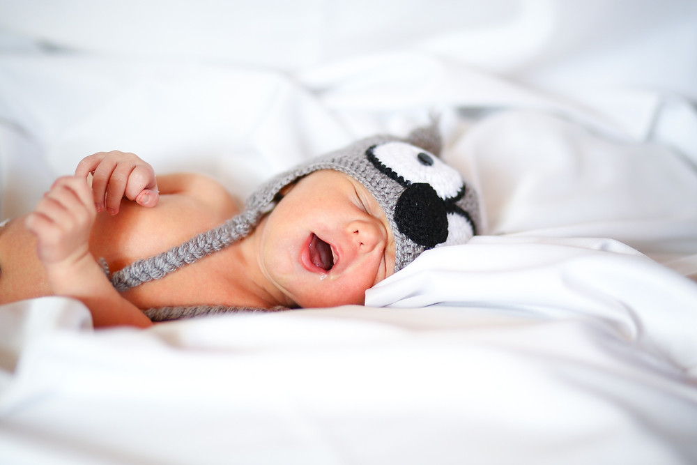 Close up of a sleeping baby with a yawing expression and wearing a knit hat with big animal character eyes and nose on the top..