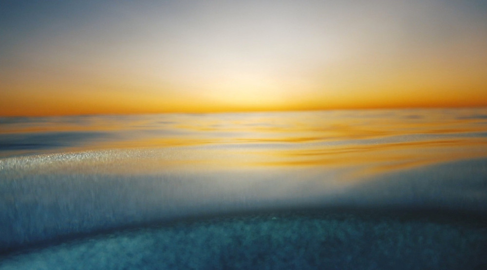 Calm blue waves against a softly lit sky during sunset.