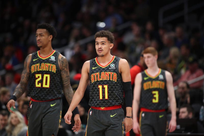 John Collins, Trae Young, and Kevin Huerter of the Atlanta Hawks walk down the court in an NBA game.