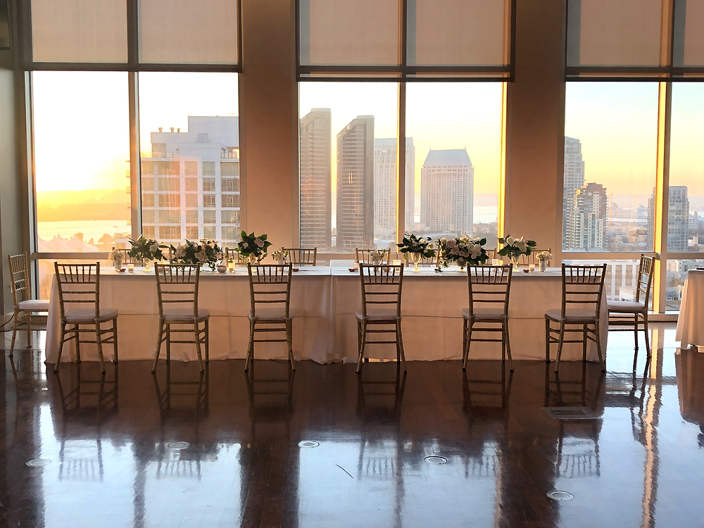 Gorgeous head table setup with multiple centerpieces with San Diego Skyline in the background. Flowers by San Diego Wedding Florist Le Champange Projects for an elegant black tie wedding at the Ultimate Skybox in downtown.