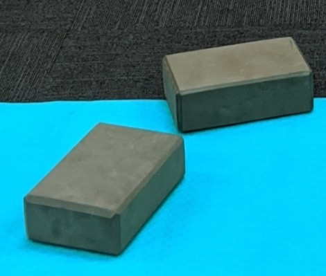Two grey foam yoga blocks on a blue yoga mat