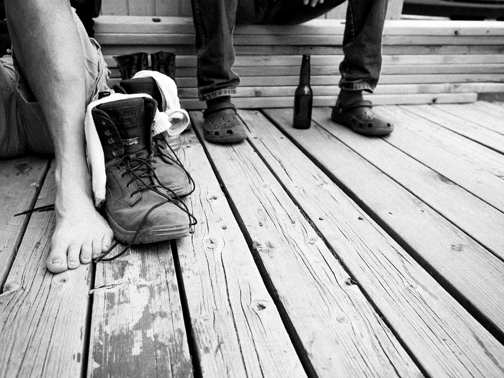 Boots and beers on a wooden porch after a long day working in the sun