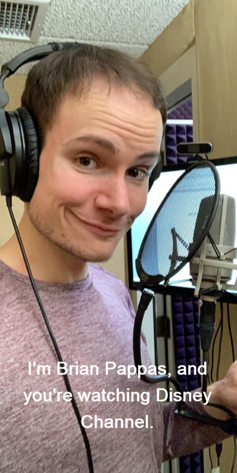 Brian Pappas in a voice acting booth with headphones a microphone and a pop filter