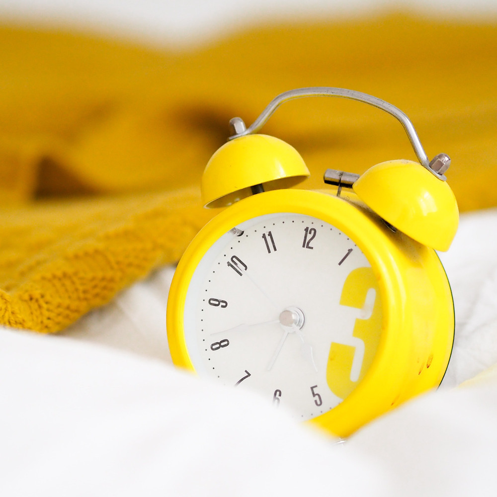 Yellow alarm clock on a bed