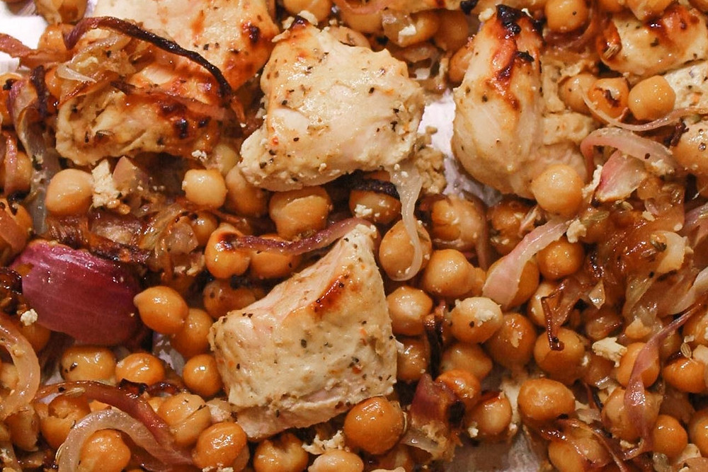 Baked chicken, caramelized onions, and chickpeas on a pan