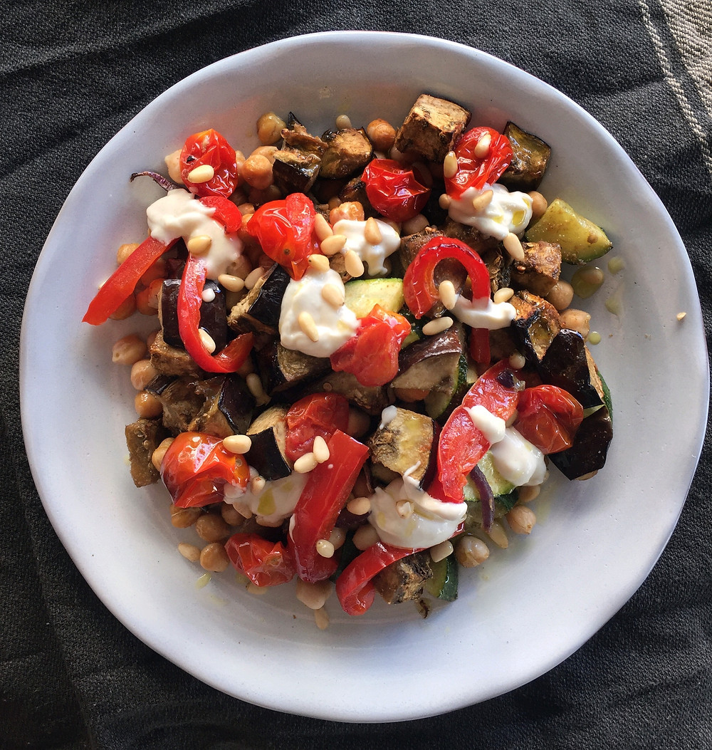 Eggplant, zucchini and chickpea salad on white plate