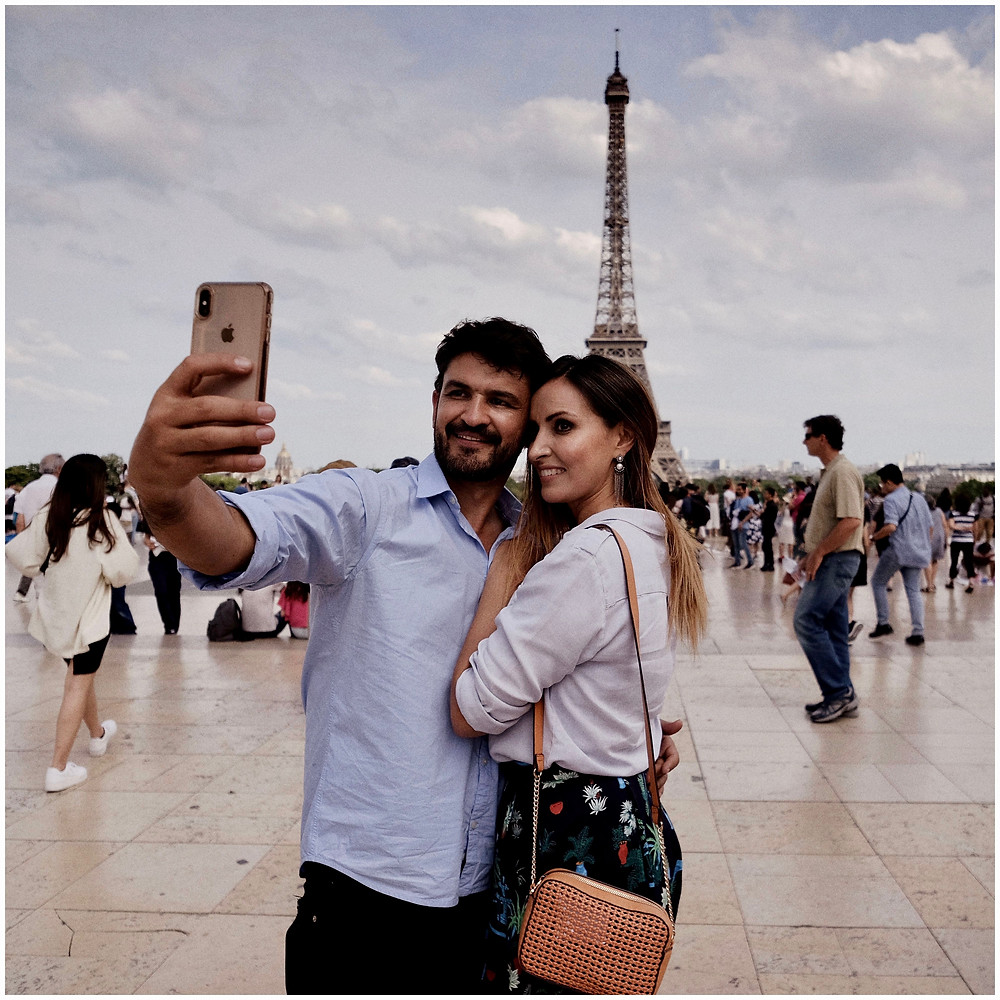 Couple taking a selfie infront of the Eiffel Tower in Paris, France