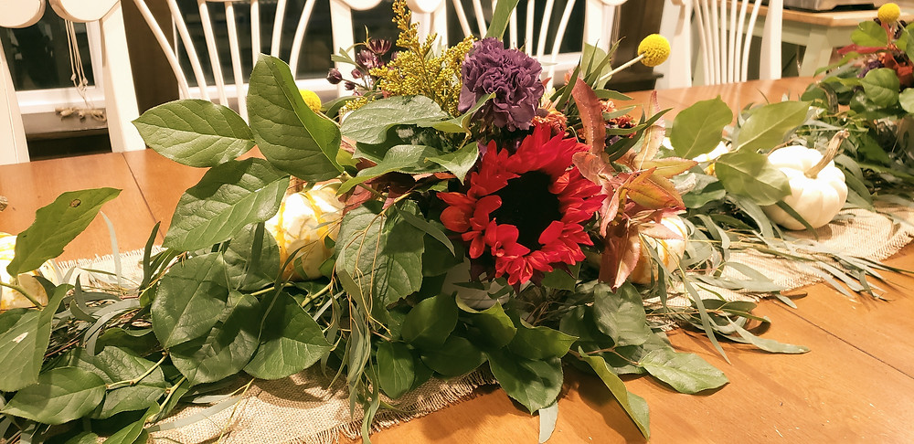Table arrangement with sunflowers, greenery and carnations.