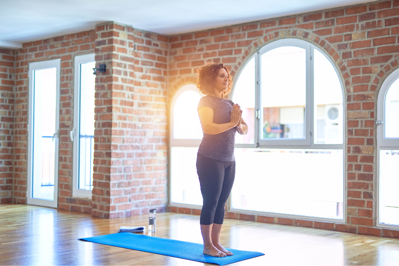 Woman in yoga studio standing with hands folded to chest