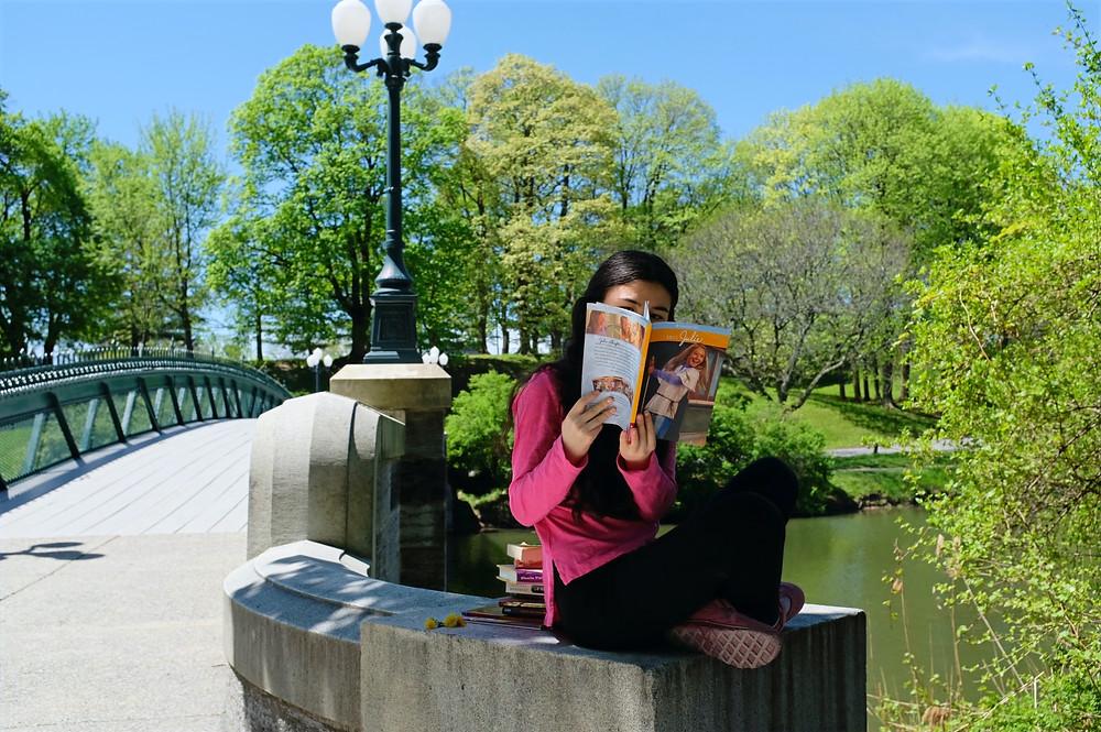 Girl sitting on ledge by footbridge reading American Girl book