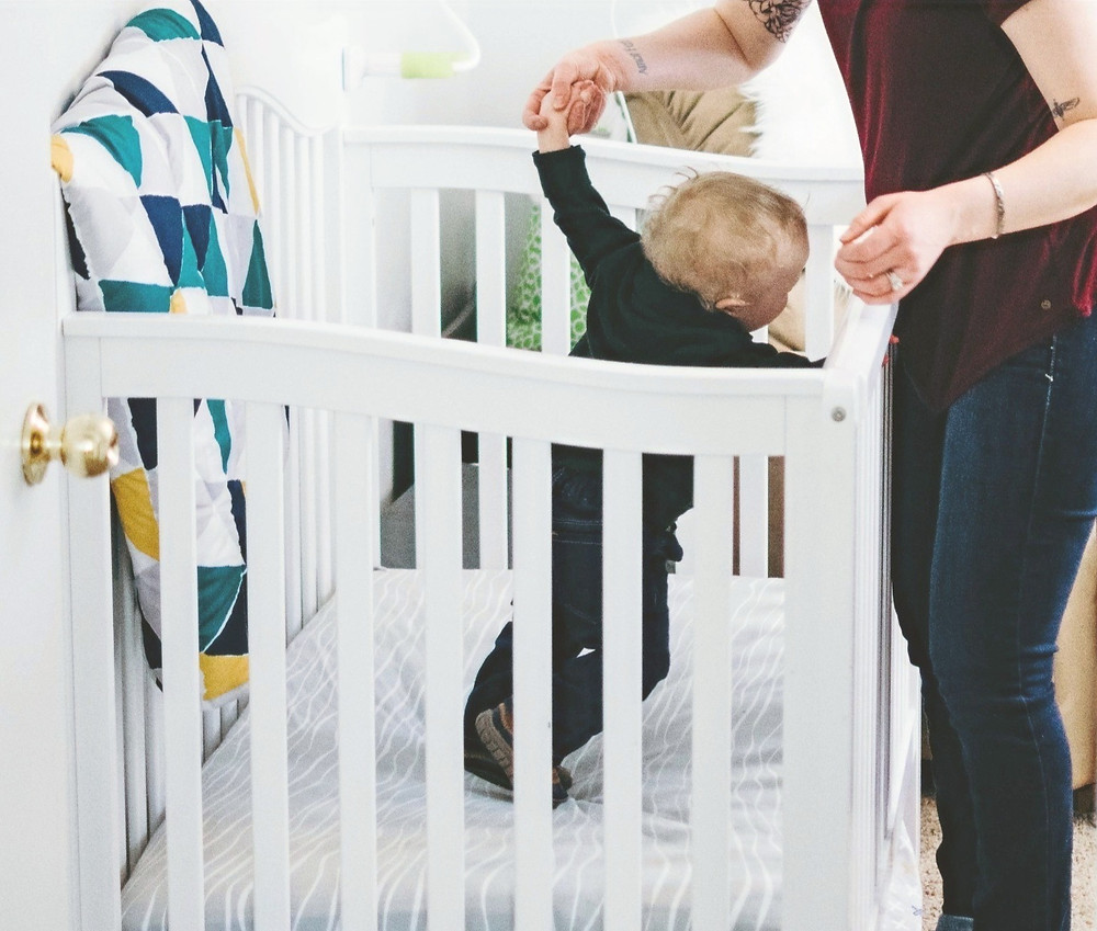 Child climbing out of cot ready for bed