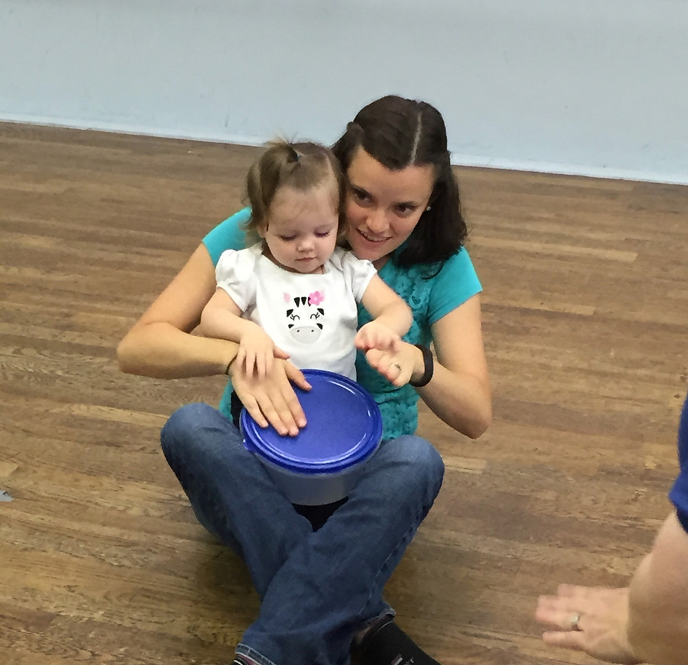 A mother and baby play a drum together at a SECE baby music class