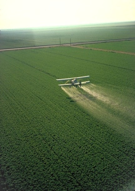 """crop duster"" airplane spraying pesticides over an agricultural field"
