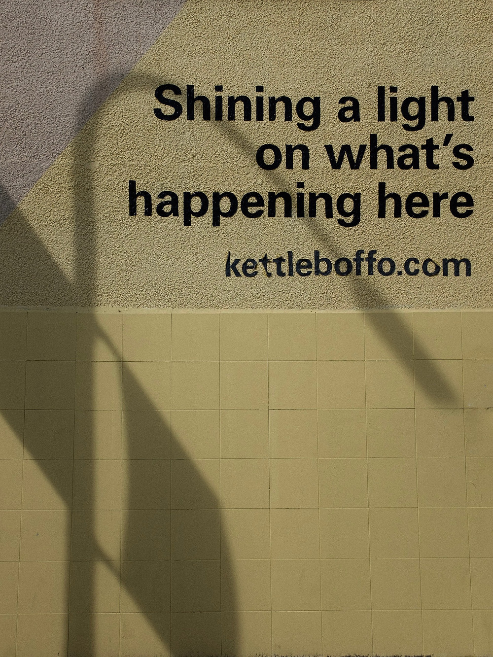 """A shadow of a lamp post is projected onto a wall: the text reads, """"Shining a light on what;s happening here..."""""""