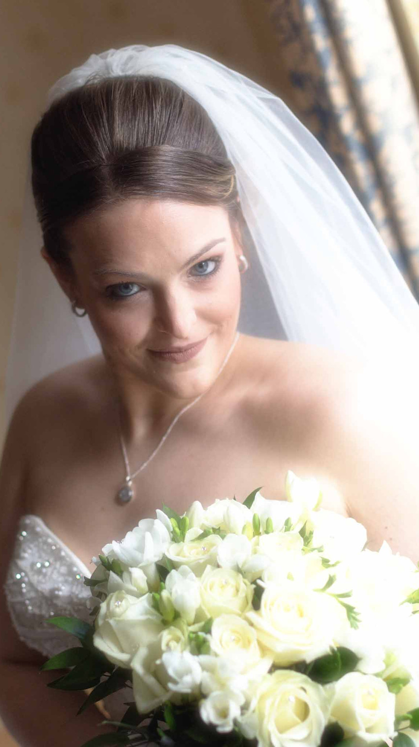 bride in a wedding dress with a veil beside a window looking at the camera