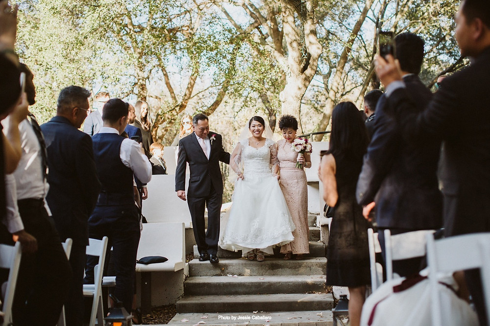 A bride walks down the aisle with the mother of the bride and the father of the bride by her side. They escort her to the groom waiting at the alter under an arch in an outdoor arena surrounded by large trees. The wedding planner fluffed her dress right before she walked onto the outdoor patio for the couple's wedding ceremony.