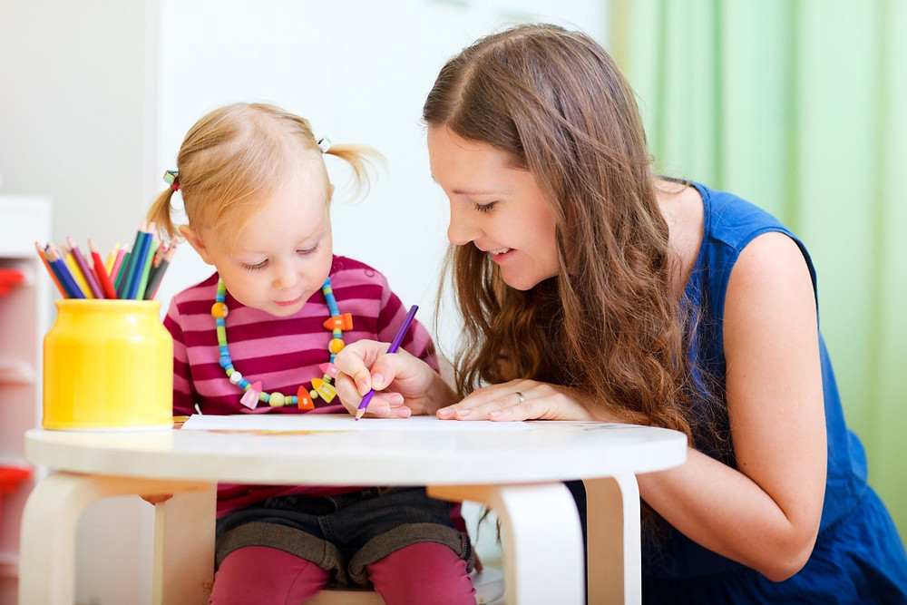 Дадилката црта цртеж со дрвена боја покрај детето кое го чува