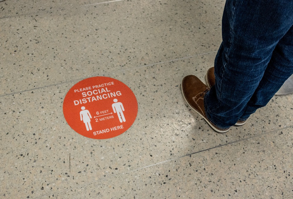 Social distancing reminder on the floor of DFW Airport.