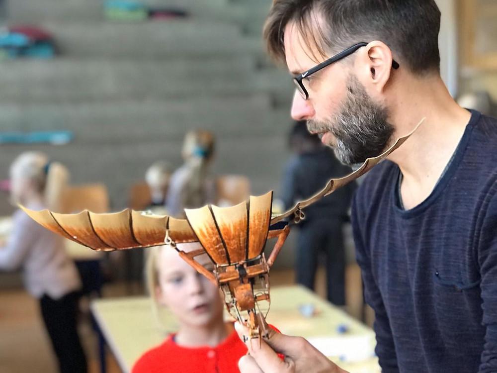 Een foto van een man met een bril die in een klas staat. In zijn hand heeft bij een vliegend sculptuur waar hij iets over verteld aan de kinderen. Een meisje kijkt aandachtig naar het sculptuur.