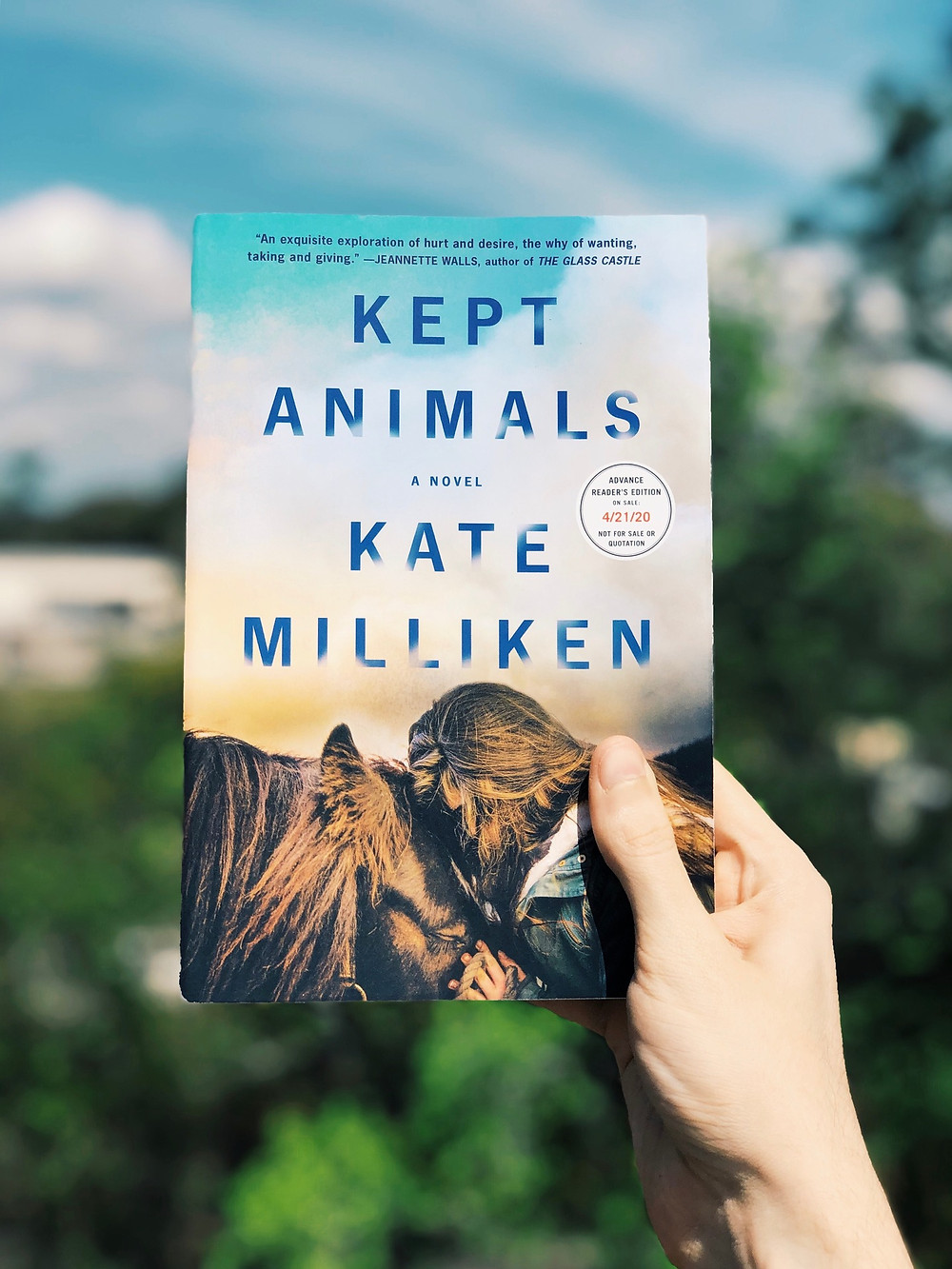 A hand holds up the book Kept Animals to a blue, sunny sky
