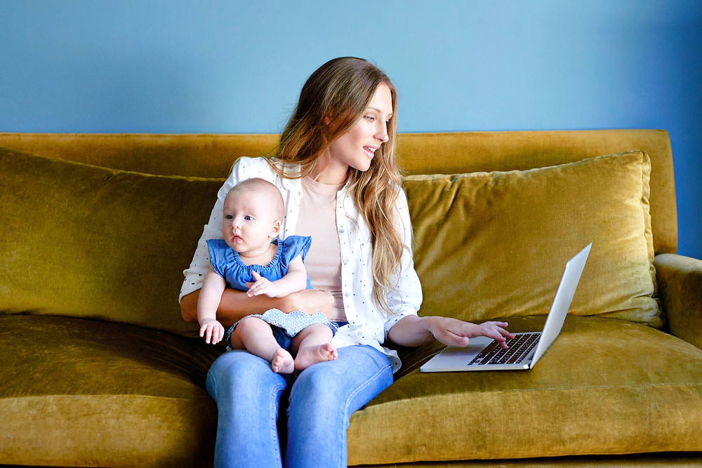 woman working on laptop while holding baby.