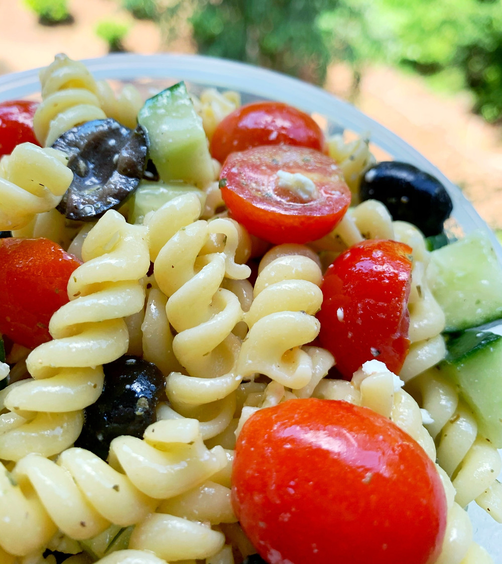 close-up of pasta salad with rotini pasta, cherry tomatoes, black olives, cucumber, and feta