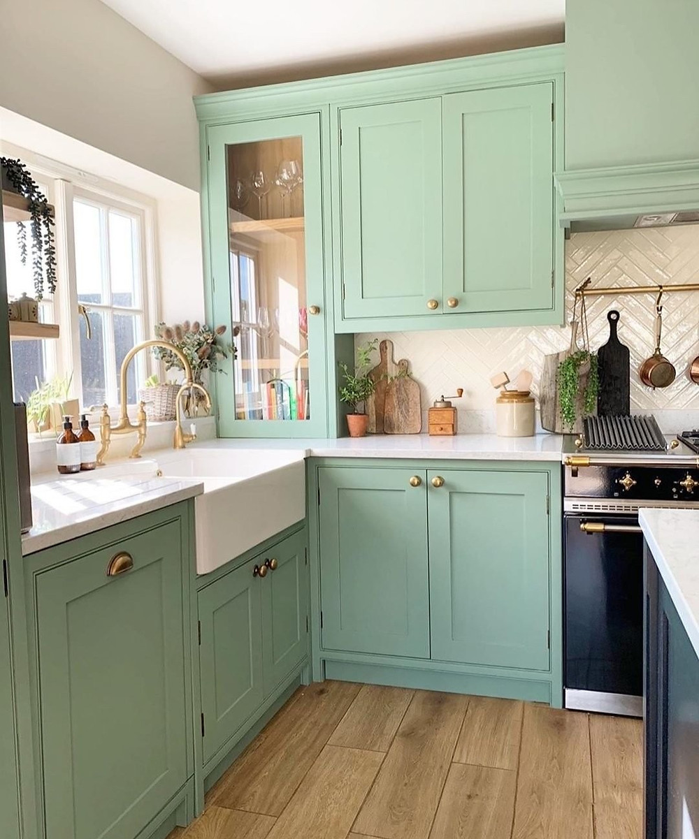 mint green kitchen cabinet colors with white countertops and hanging pans and pots